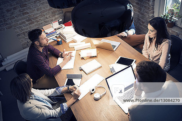 High angle view of colleagues having discussion in meeting