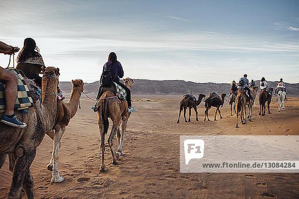 Touristen reiten auf Kamelen in der Wüste gegen den Himmel