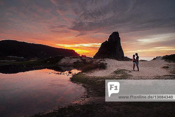Romantisches Paar  das bei Sonnenuntergang auf Sand gegen den Himmel steht