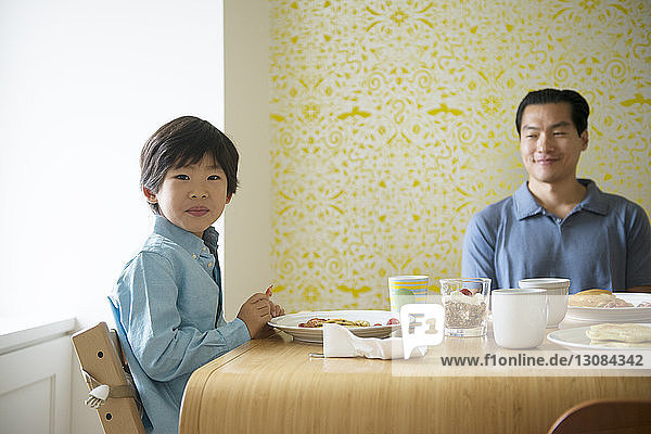 Portrait of boy having food with father at table