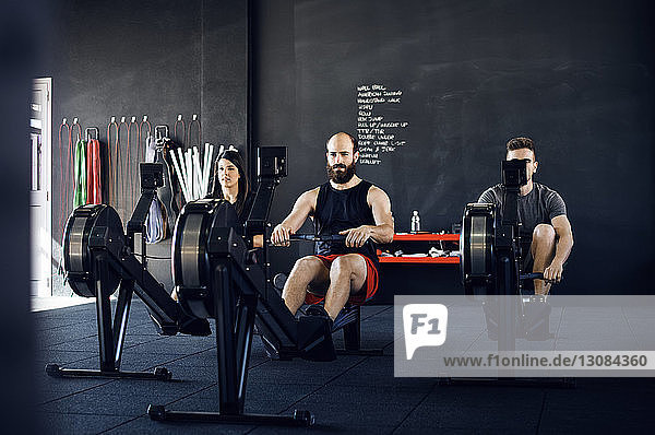 Determined athletes exercising on rowing machine at gym