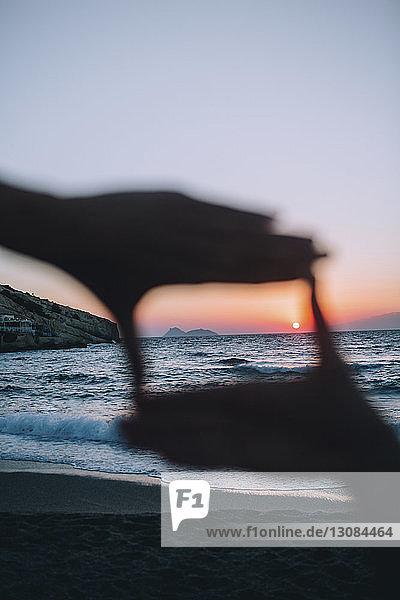 Sonne durch den Rahmen der Hände gegen den Himmel am Strand gesehen