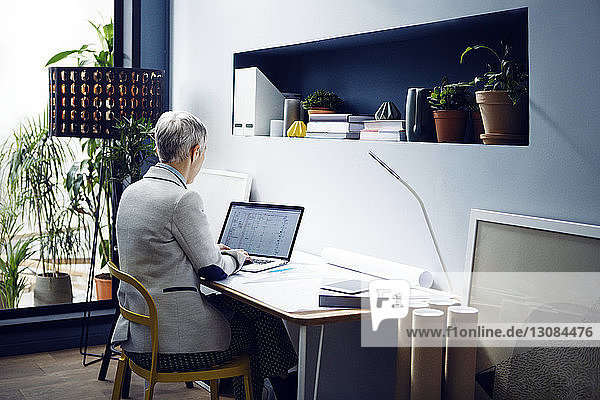 Female architect using laptop at table in office