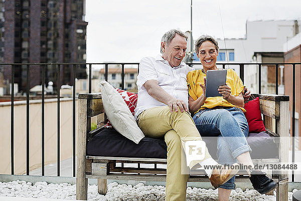 Happy senior couple using tablet computer while sitting on bench at terrace