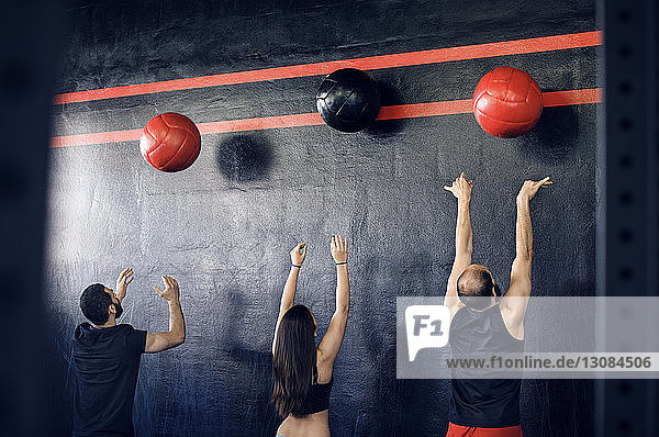 Rear view of athletes exercising with medicine balls in gym