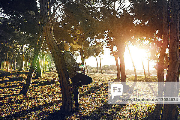 Jogger relaxing while leaning on tree in park at morning