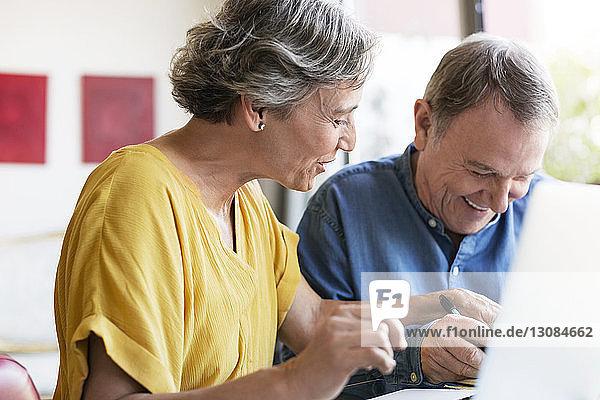 Fröhliches älteres Ehepaar plant Urlaub zu Hause