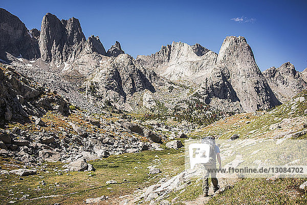 Rückansicht eines Wanderers  der auf dem Feld durch Felsformationen geht