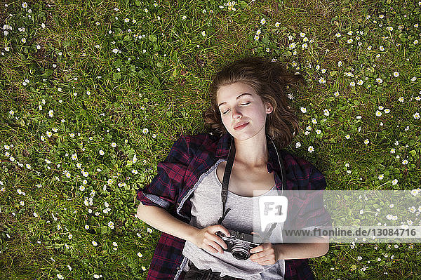 Overhead view of woman holding camera while lying on grass at park