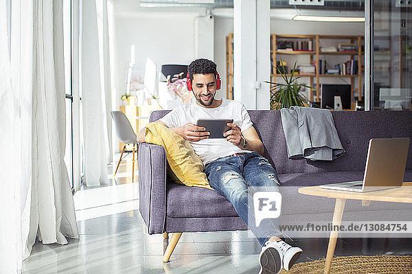 Glücklicher Geschäftsmann mit Tablet-Computer während er sich im Büro auf dem Sofa entspannt