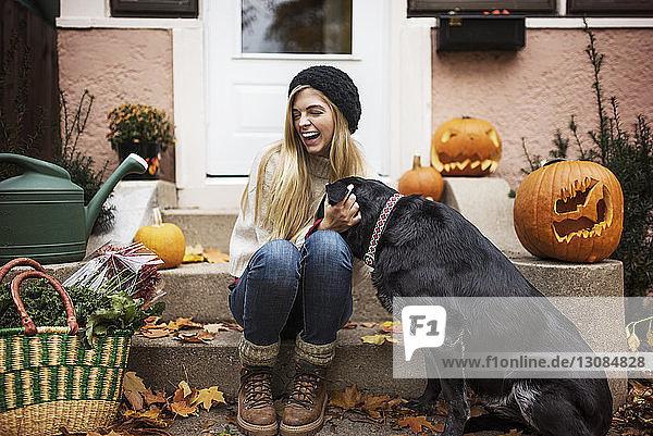 Glückliche Frau berührt Hund  während sie auf einer Treppe sitzt