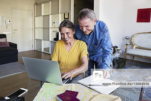 Glückliches älteres Ehepaar benutzt Laptop  während es seinen Urlaub zu Hause plant