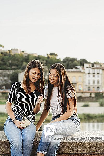 Freunde betrachten ein Sofortbild  während sie auf einer Stützmauer am Arno-Fluss vor klarem Himmel sitzen