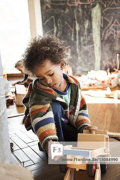 Junge im Pullover spielt zu Hause mit Spielzeug