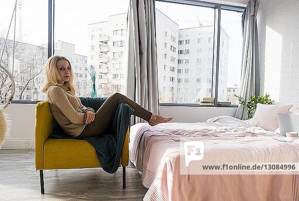 Porträt einer Frau  die sich zu Hause auf einem Sessel im Schlafzimmer entspannt