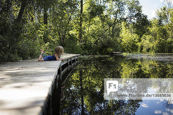 Side view of girl lying on pier by lake