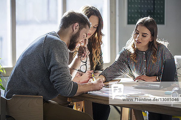 University students studying while sitting at table in classroom