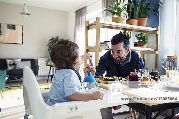 Happy father playing with son while having breakfast at home