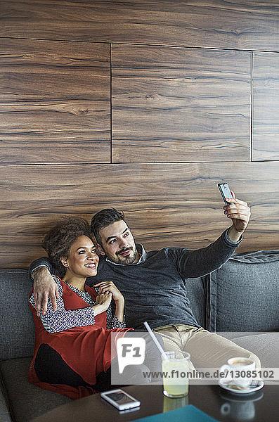 Lächelndes Geschäftspärchen  das sich auf dem Sofa sitzend im Cafe Selbsthilfe nimmt