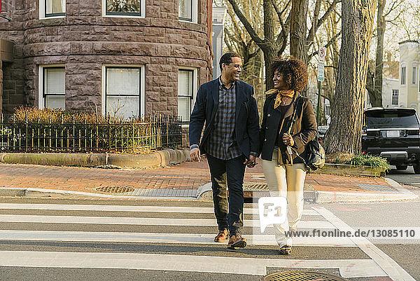 Glückliches Paar in voller Länge beim Überqueren der Straße an den Händen halten