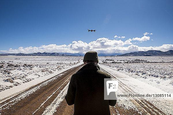 Rückansicht eines Mannes  der im Winter in der Wüste Drohnen gegen den Himmel fliegt