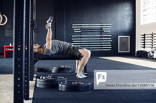 Side view of man lifting weight bar while lying on table in gym