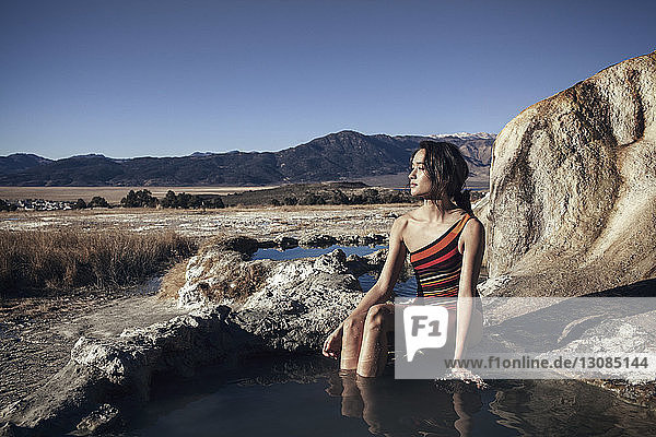 Thoughtful woman relaxing at Bridgeport Hot Springs against clear sky