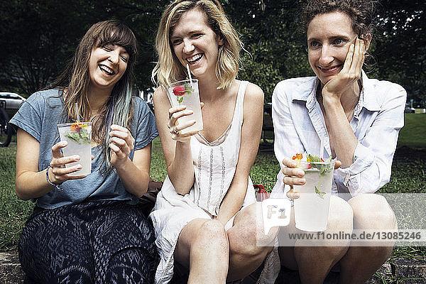 Happy friends enjoying drink while sitting at backyard