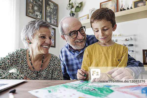 Happy grandparents looking at grandson making drawing at home