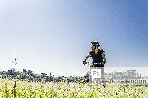 Young man with mountain bike on grassy field against clear sky during sunny day