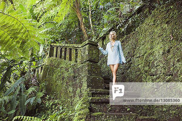 Nachdenklich-sinnliche Frau steht auf bemoosten Stufen im Wald