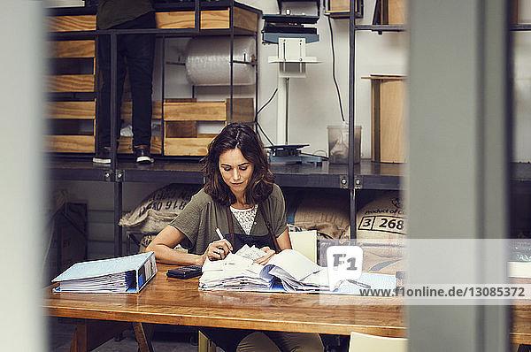 Reife Besitzerin analysiert Dokumente bei Tisch im Café