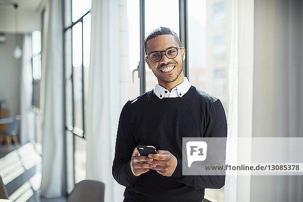 Porträt eines Geschäftsmannes  der ein Mobiltelefon benutzt  während er am Fenster im Büro steht