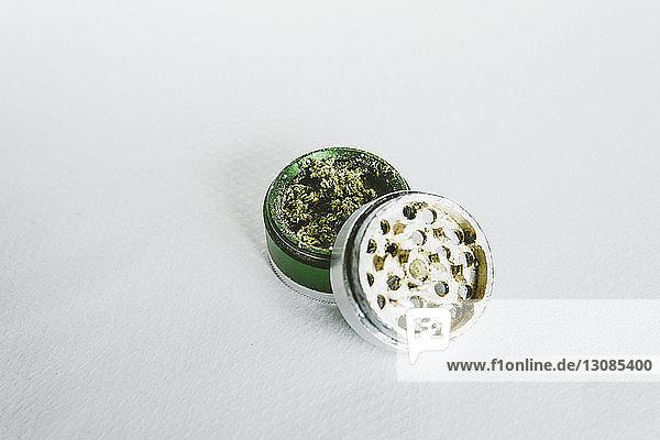 Nahaufnahme von Marihuana in der Mühle auf weißem Tisch