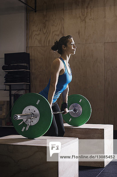 Side view of determined female athlete lifting barbell in health club