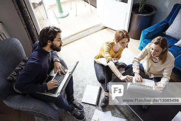 Hochwinkelansicht von kreativen Menschen  die Laptops im Büro benutzen