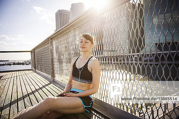 Woman listening music while relaxing against railing on sunny day