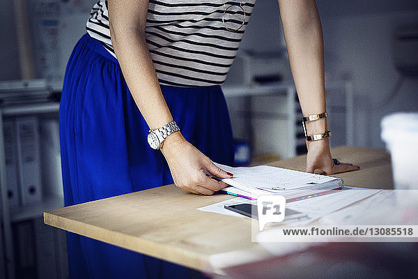 Midsection of businesswoman with book at desk in office