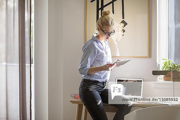 Frau benutzt Tablet-Computer  während sie zu Hause am Tisch sitzt