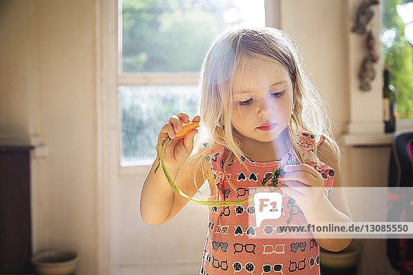 Süßes Mädchen hält zu Hause Karotte