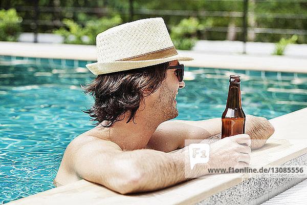 Seitenansicht eines Mannes  der eine Bierflasche im Schwimmbad hält