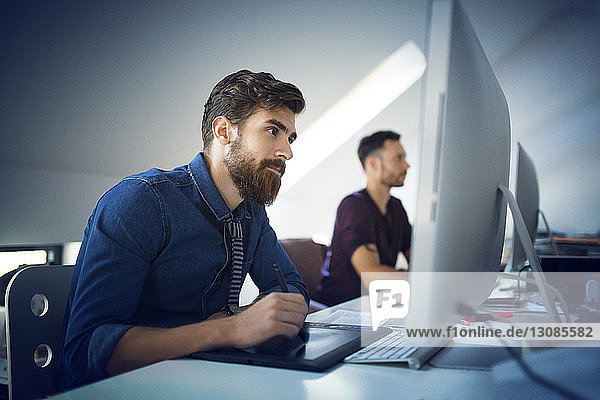 Businessman using pen tablet while working by colleague at desk in office