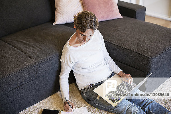 High angle view of mature woman writing while using laptop at home