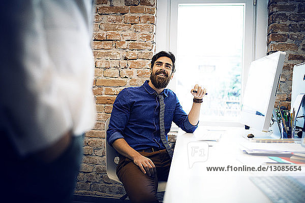 Businessman looking at colleague while sitting at desk in office