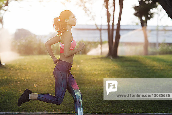 Seitenansicht einer Frau  die an einem sonnigen Tag im Park joggt