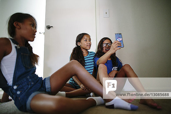 Female friends taking selfie with girl sitting in foreground at home