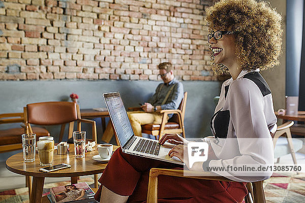 Side view of happy businesswoman looking away while using laptop at hotel lobby