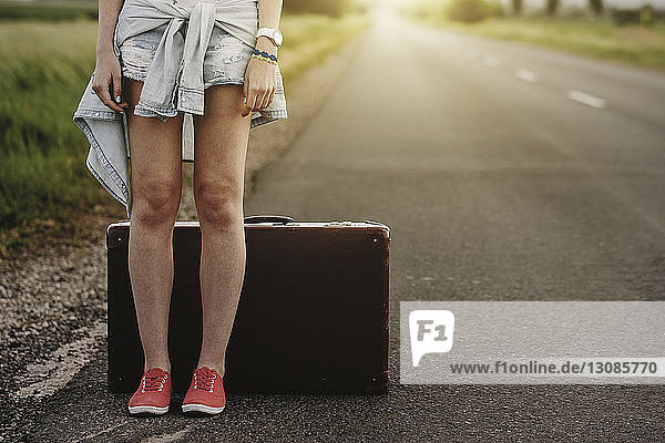 Low section of woman standing by suitcase on road