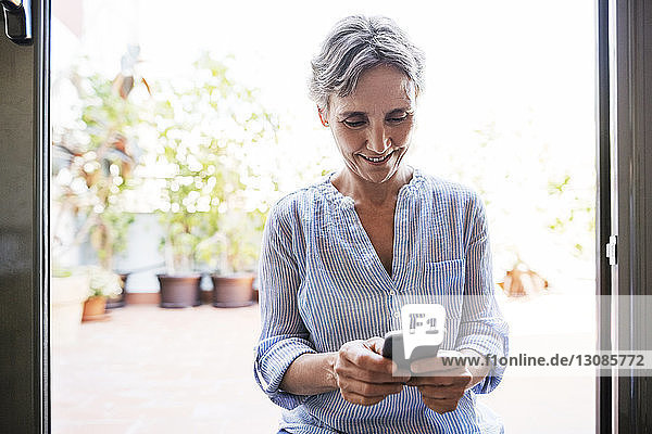 Happy mature woman using smart phone while sitting by window at home