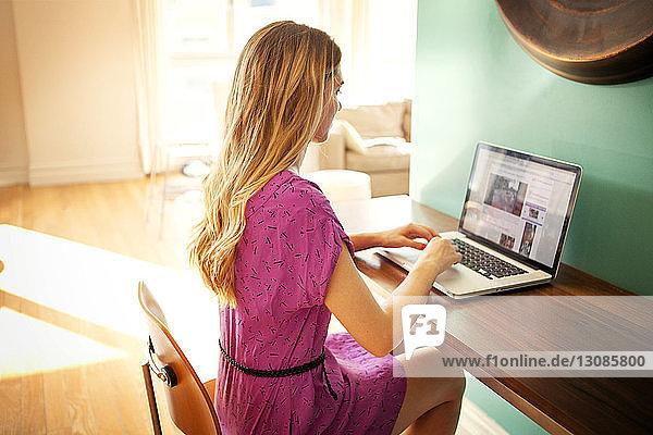 Junge Frau  die an sonnigen Tagen einen Laptop am Tisch im Haus benutzt